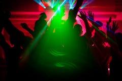 Mensen die in club met lightshow dansen stock afbeelding