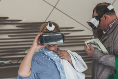 Mensen die 3D hoofdtelefoon proberen in Expo 2015 in Milaan, Italië Stock Afbeeldingen