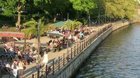 Mensen die in de avond zon bij de koffie van de Fuifrivier in Berlijn zitten stock footage