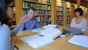 Mensen die in de bibliotheek bestuderen terwijl spreken stock video