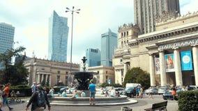 Mensen die in de fontein dichtbij Paleis van Cultuur en Wetenschap en Teatr Dramatyczny in Warshau rusten, stock footage