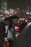 Mensen die in de regen lopen Stock Foto's