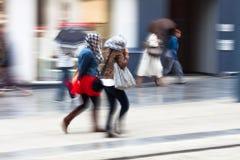Mensen die in de regenachtige stad lopen Stock Foto's