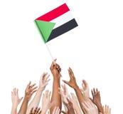 Mensen die de Vlag van de Soedan houden Royalty-vrije Stock Foto