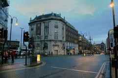 Mensen die de weg op headrow in de stadscentrum die van Leeds kruisen bij schemering neer naar eastgate kijken Royalty-vrije Stock Afbeelding