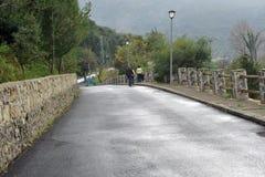 Mensen die de weg op de rand van Benamahoma-dorp na regen, Andalusia, Spanje lopen Royalty-vrije Stock Foto