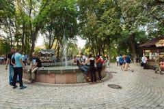 Mensen die dichtbij fontein in populair Shevchenko-park ontspannen Stock Afbeelding