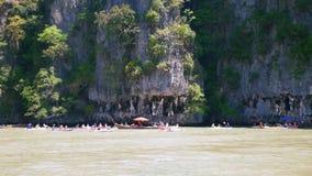 Mensen die dichtbij rotsachtige kust en holen kayaking stock videobeelden