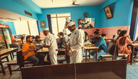 Mensen die diner binnen de kleurrijke Indische koffie met bezige kelners hebben Royalty-vrije Stock Afbeelding