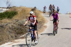 Mensen die door fiets in de stad in Milos, Griekenland gaan Heel wat tou Stock Afbeeldingen