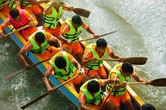 Mensen die draakboot in het rennen roeien Stock Foto's