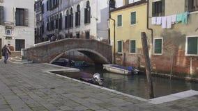 Mensen die een brug kruisen die een klein kanaal in Venetië overspant stock video
