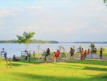 Mensen die in een park langs de rivier, achtergrond, behang, hemel uitoefenen Stock Afbeelding