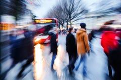 Mensen die een stadsstraat kruisen bij schemer Royalty-vrije Stock Foto