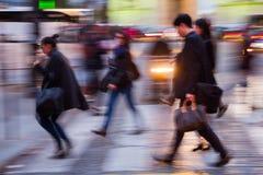 Mensen die een straat kruisen bij nacht Royalty-vrije Stock Foto