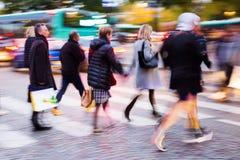 Mensen die een straat kruisen bij nacht Royalty-vrije Stock Foto's