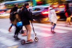 Mensen die een straat kruisen bij nacht Royalty-vrije Stock Afbeelding