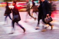 Mensen die een straat kruisen bij nacht Stock Fotografie