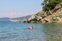 Mensen die een sunbath nemen en op de kust van het overzees zwemmen Stock Afbeeldingen
