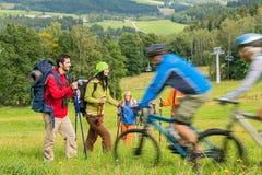 Toeristen die en de zomeraard wandelen berijden van bergfietsen Royalty-vrije Stock Foto
