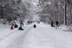 Mensen die en omhoog de sneeuw behandelde weg op Moun lopen tobogganning Stock Fotografie