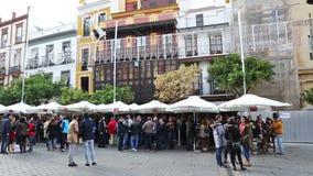 Mensen die en op een straat van de stad van Sevilla ontspannen drinken stock videobeelden