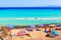 Mensen die en op het strand van het Egeïsche overzees zonnebaden zwemmen Stock Foto