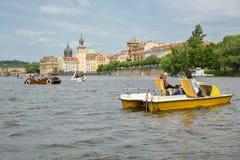 Mensen die en in peddelboten op Vltva-rivier berijden ontspannen stock afbeelding
