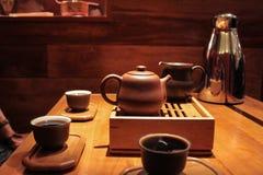 3 mensen die en zeer donkere thee pu proeven drinken -pu-erh in kleine proevende koppen stock afbeelding