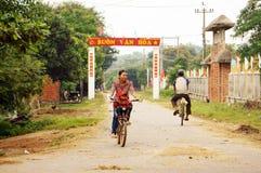 Mensen die fiets berijden bij platteland Stock Afbeeldingen