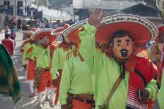 Mensen die, gebruikend maskers begroeten die, als mariachi met groene overhemden en oranje hoeden worden vermomd royalty-vrije stock foto's