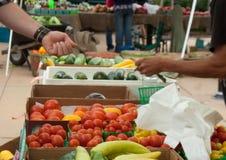 Mensen die geld ruilen bij landbouwersmarkt Stock Afbeeldingen
