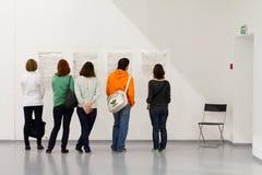 Mensen die gesprek lezen bij de tentoonstelling Royalty-vrije Stock Afbeeldingen