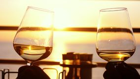 Mensen die glas die wijn houden, een toost over zonsondergang maken Vrienden die witte wijn, het roosteren drinken royalty-vrije stock afbeelding