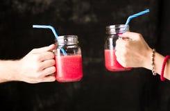 Mensen die glazen met watermeloen clinking smoothie Stock Foto
