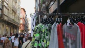 Mensen die goedkope t-shirts op straat het winkelen boxen kiezen bij lokale bazaar stock video