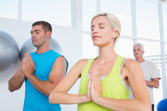 Mensen die in gymnastiekklasse mediteren Stock Foto's