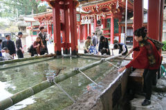Mensen die hand met het wijwater voor Dazaifu-tenmangu wassen Stock Foto's