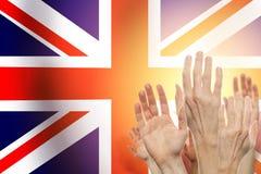 Mensen die handen en de vlag van het Verenigd Koninkrijk op achtergrond opheffen Patriottisch concept royalty-vrije stock foto