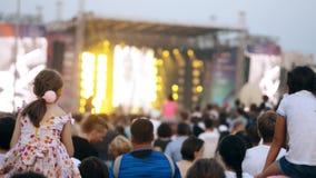 Mensen die in het stadium in festival van de de zomer het openluchtmuziek bekijken stock video