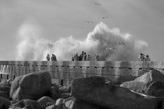 Mensen die het stormachtige overzees bekijken Stock Foto's