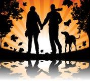 Mensen die hun hond in de Bladeren van de Herfst lopen Royalty-vrije Stock Foto's