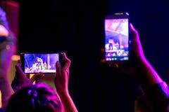 Mensen die hun slimme telefoons houden en overleg fotograferen stock fotografie