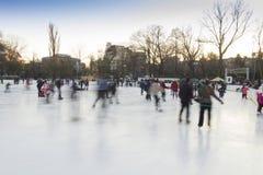 Mensen die ijs het schaatsen van piste genieten Stock Afbeelding