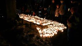 Mensen die kaarsen op gedenkteken verlaten bij Kalevankangas-Begraafplaats stock footage