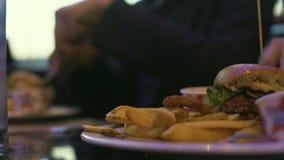 Mensen die in koffie zitten die en caloriehamburger meedelen eten met frieten stock videobeelden