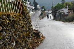 Mensen die langs de weg op de rand van Benamahoma-dorp na regen, Andalusia, Spanje lopen Royalty-vrije Stock Afbeeldingen