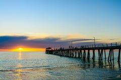 Mensen die langs pier bij zonsondergang wailking Royalty-vrije Stock Foto