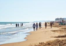Mensen die langs zandig strand lopen stock afbeeldingen