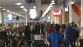 Mensen die in Luchthaven lopen Defocusachtergrond van bezige grote luchthaven met mensen die langs het wachten lopen hal Langzame stock video